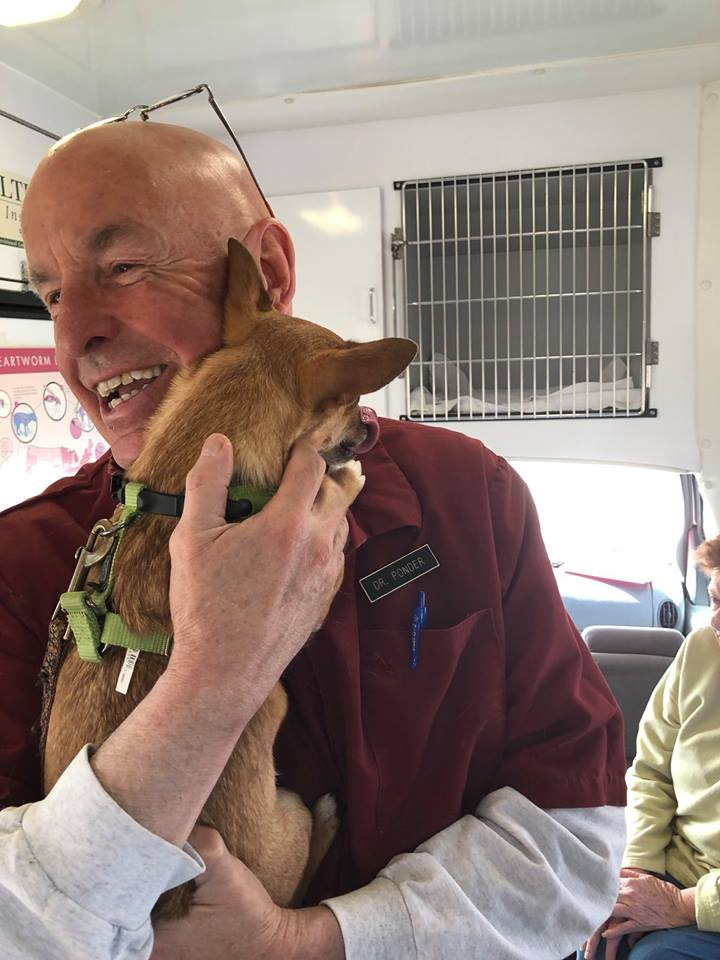 Dr. Ponder smiling and hugging a small brown dog inside of the mobile clinic